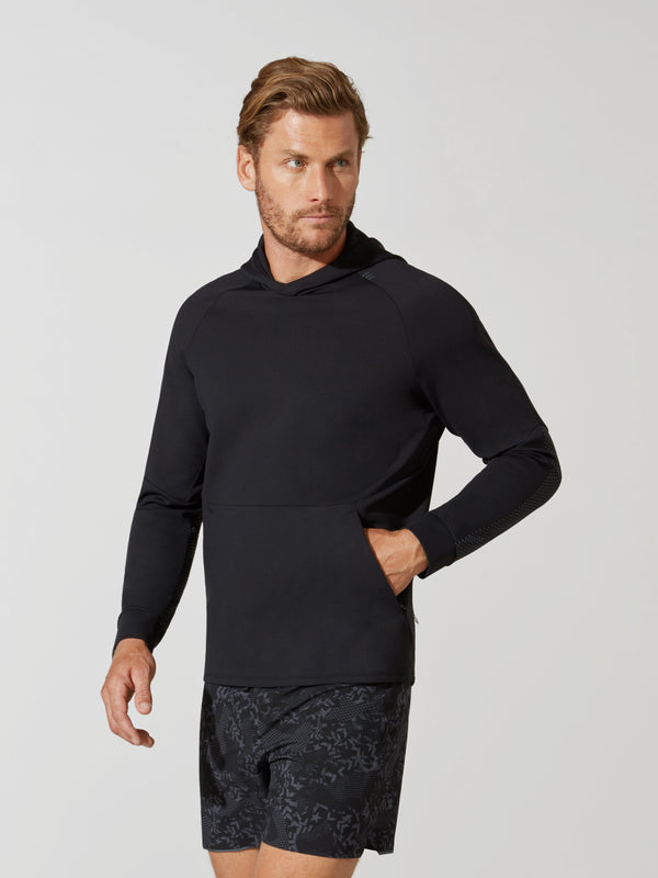 front view of male model in black hooded pullover sweatshirt and dark and light grey patterned athletic shorts