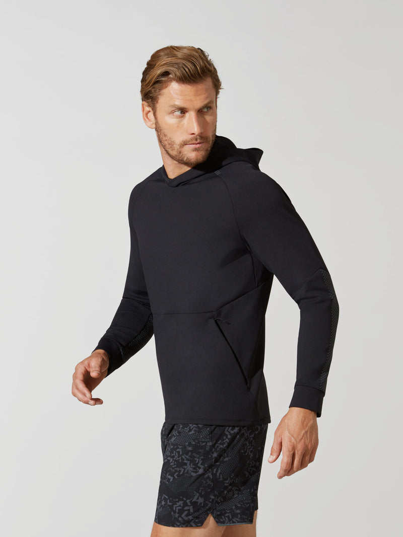 side view of male model in black hooded pullover sweatshirt and dark and light grey patterned athletic shorts