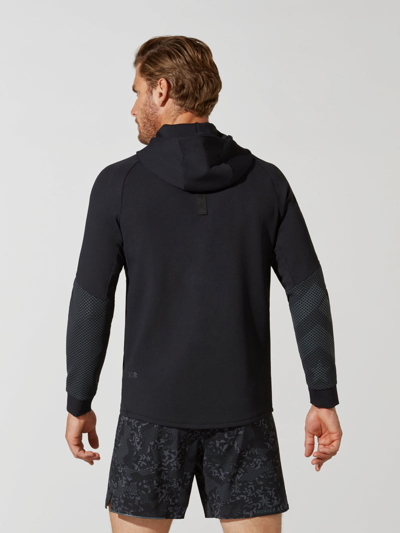 back view of male model in black hooded pullover sweatshirt and dark and light grey patterned athletic shorts