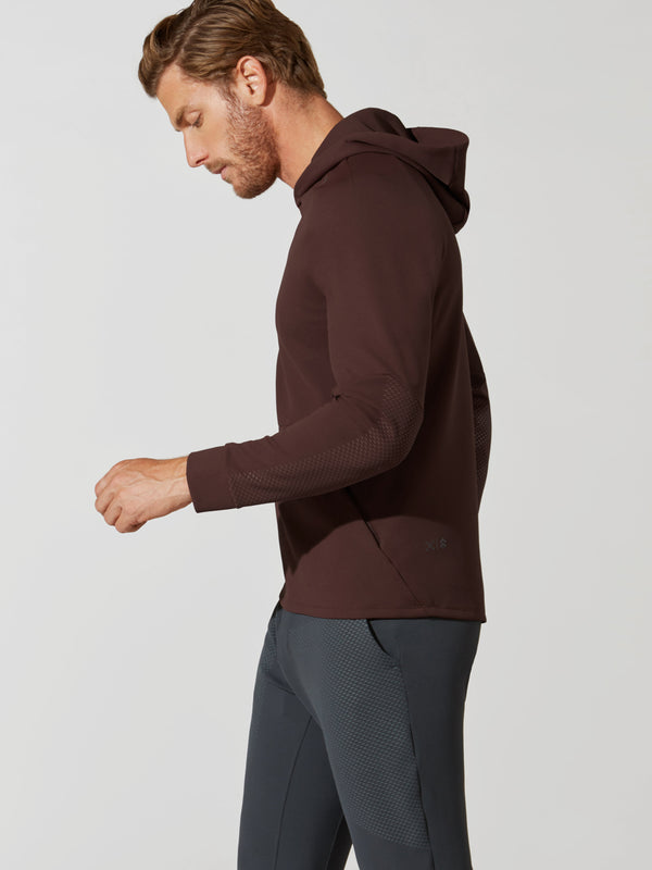 side view of male model in maroon hooded sweatshirt and dark grey barry's bootcamp detailed sweatpants