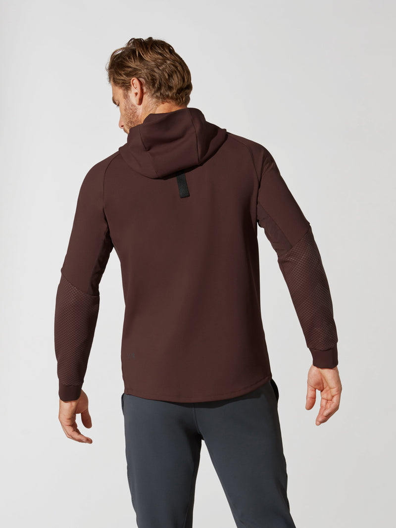 back view of male model in maroon hooded sweatshirt and dark grey barry's bootcamp detailed sweatpants