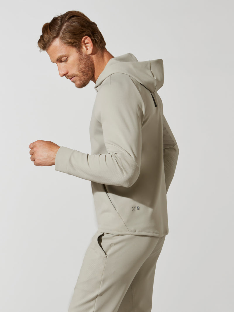 side view of male model in sand colored hooded sweatshirt and matching sweatpants