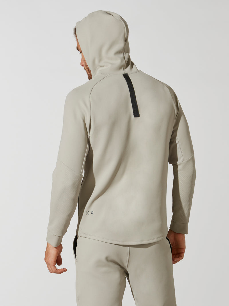 back view of male model in sand colored hooded sweatshirt with hood up and matching sweatpants