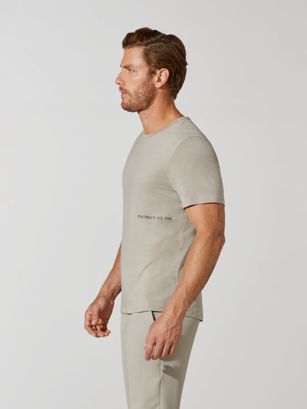 "side view of male model in sand colored t-shirt with ""stronger as one"" written under rib and matching sweatpants"