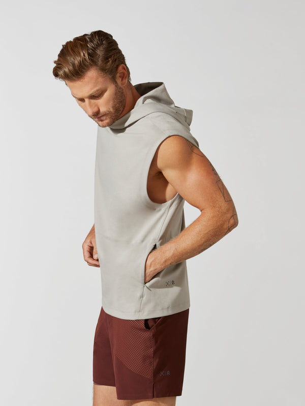 side view of male model in sleeveless light grey hoodie and maroon athletic shorts