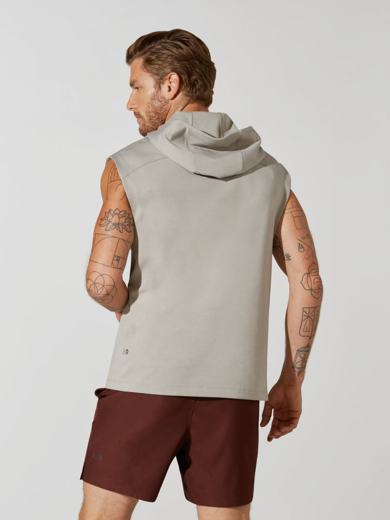 back view of male model in sleeveless light grey hoodie and maroon athletic shorts
