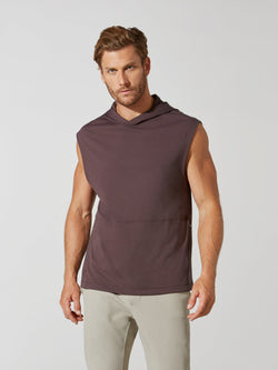 front view of male model in sleeveless heathered maroon hoodie and sand colored athletic sweatpants