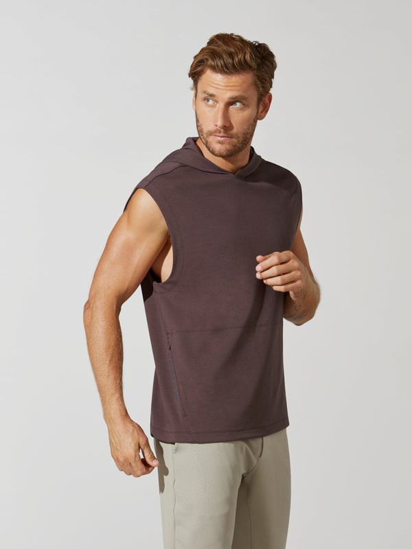 side view of male model in sleeveless heathered maroon hoodie and sand colored athletic sweatpants
