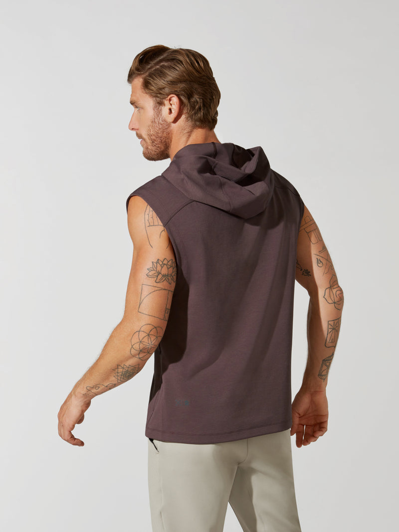 back view of male model in sleeveless heathered maroon hoodie and sand colored athletic sweatpants