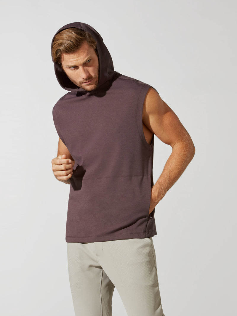 front view of male model in sleeveless heathered maroon hoodie with hood up and sand colored athletic sweatpants