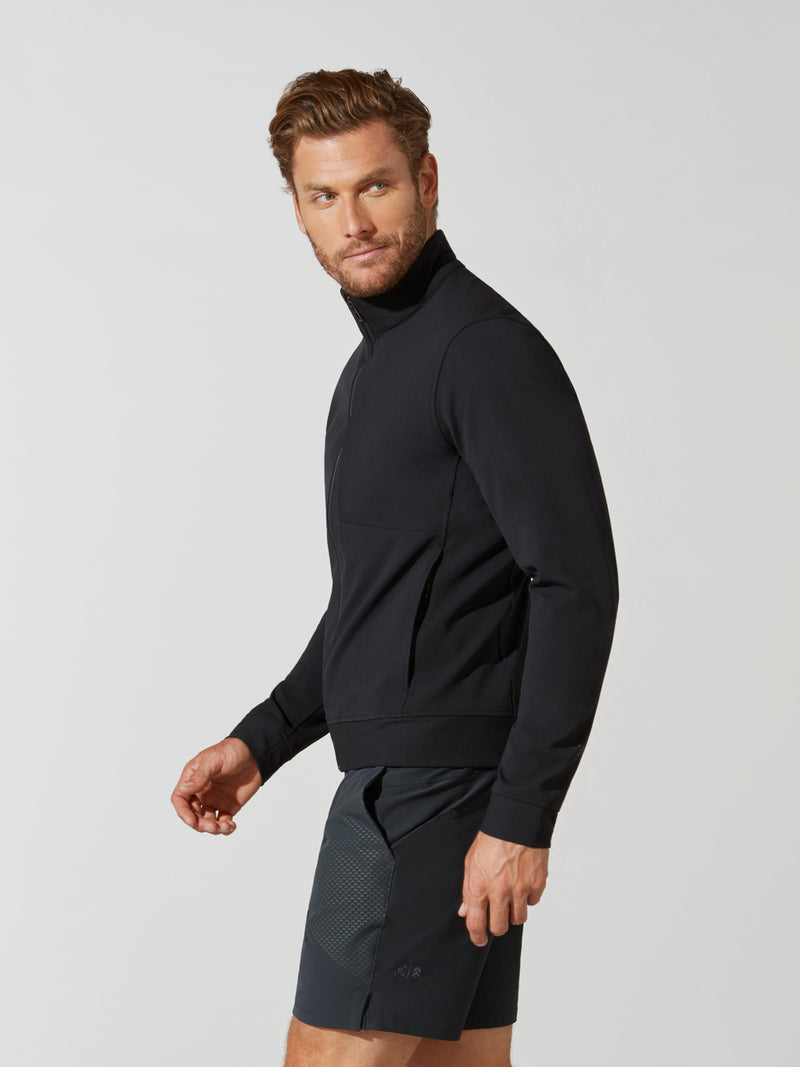 side view of male model in black zip up athletic jacket and dark grey shorts