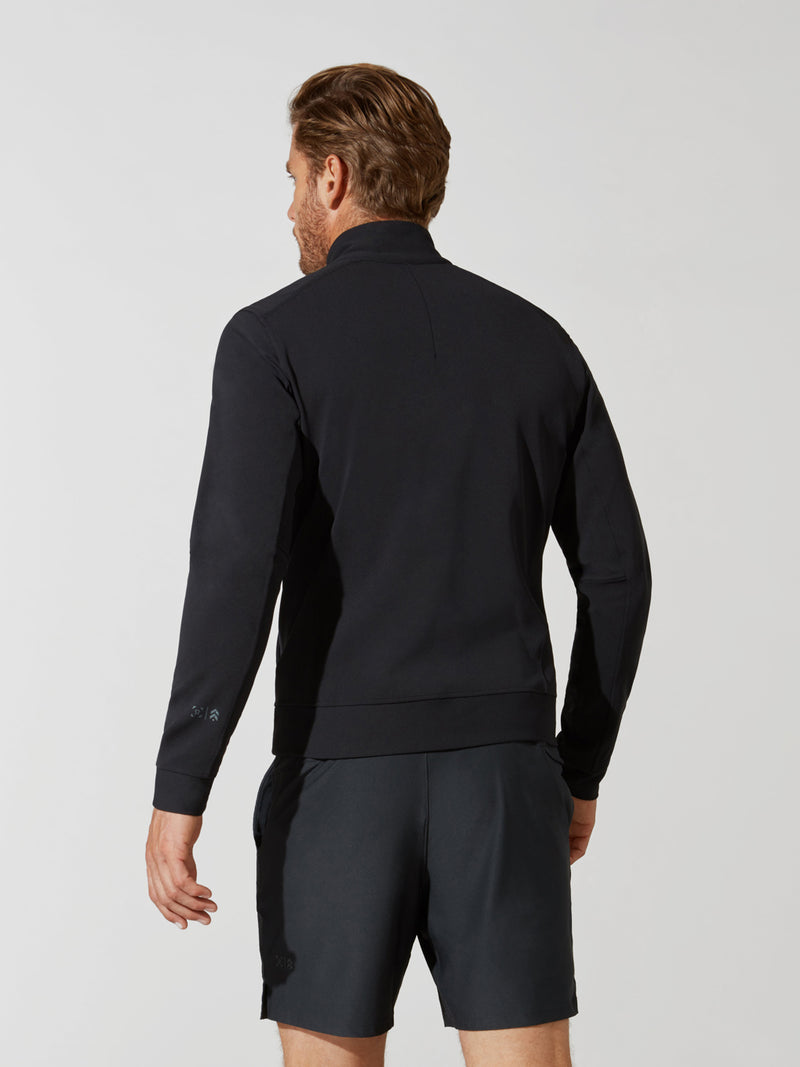 back view of male model in black zip up athletic jacket and dark grey shorts