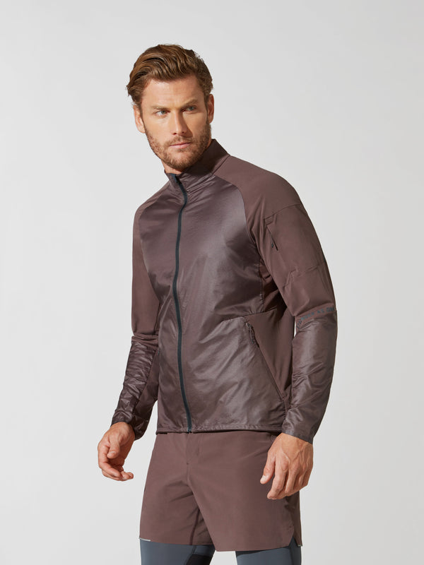side view of male model in shiny mauve athletic jacket and matching mauve shorts
