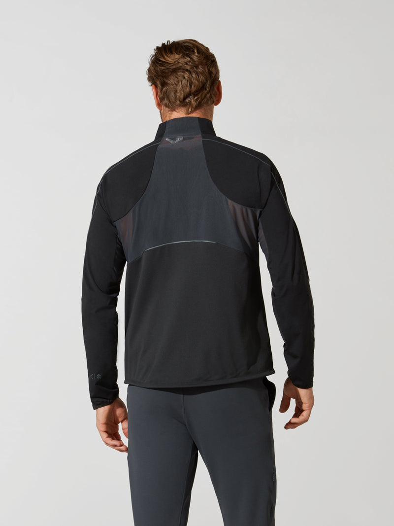 back view of male model in shiny black athletic jacket and dark grey athletic leggings