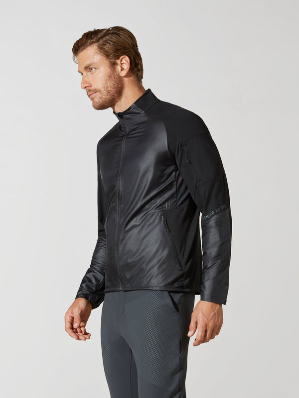 side view of male model in shiny black athletic jacket and dark grey athletic leggings