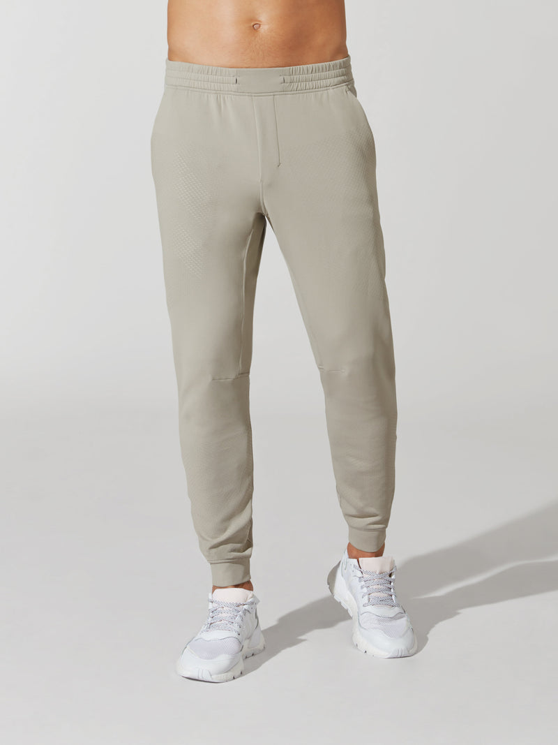 front view of male model in sand skinny sweatpants and white sneakers