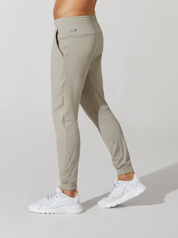 side view of male model in sand skinny sweatpants and white sneakers