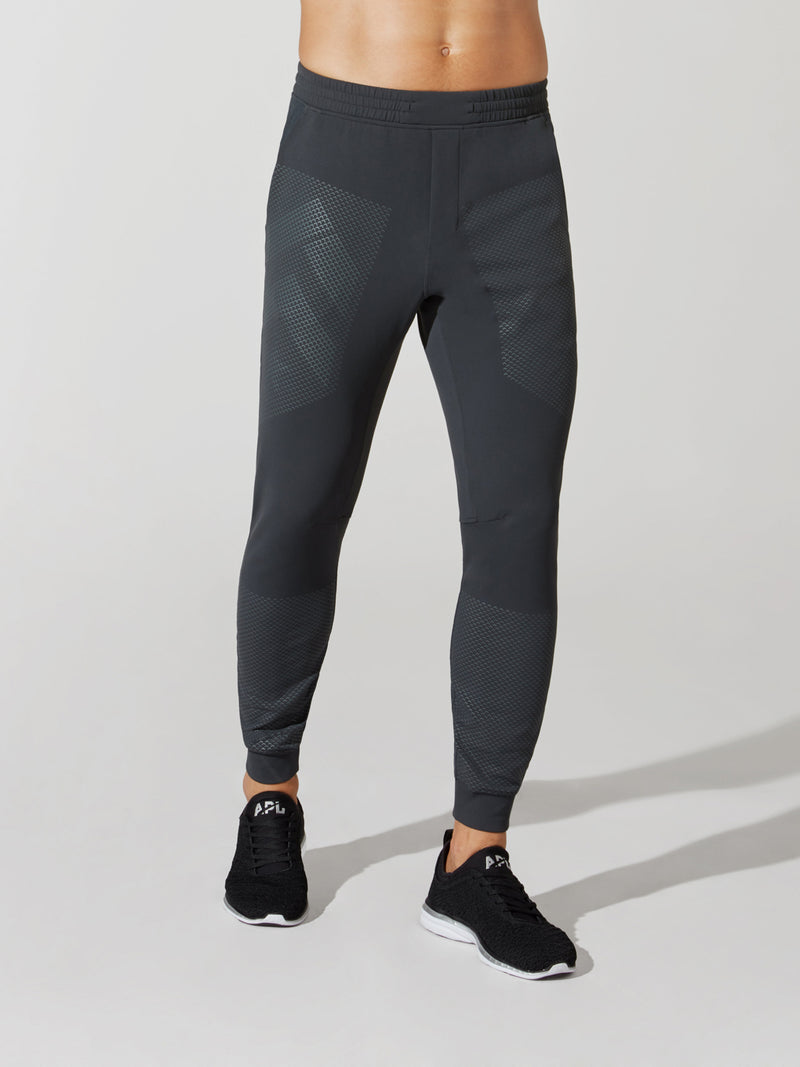 front view of male model in dark grey sweatpants with barry's bootcamp logo detail on thigh and black sneakers