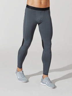 front view of male model in light grey full length leggings with black waistband and light blue sneakers