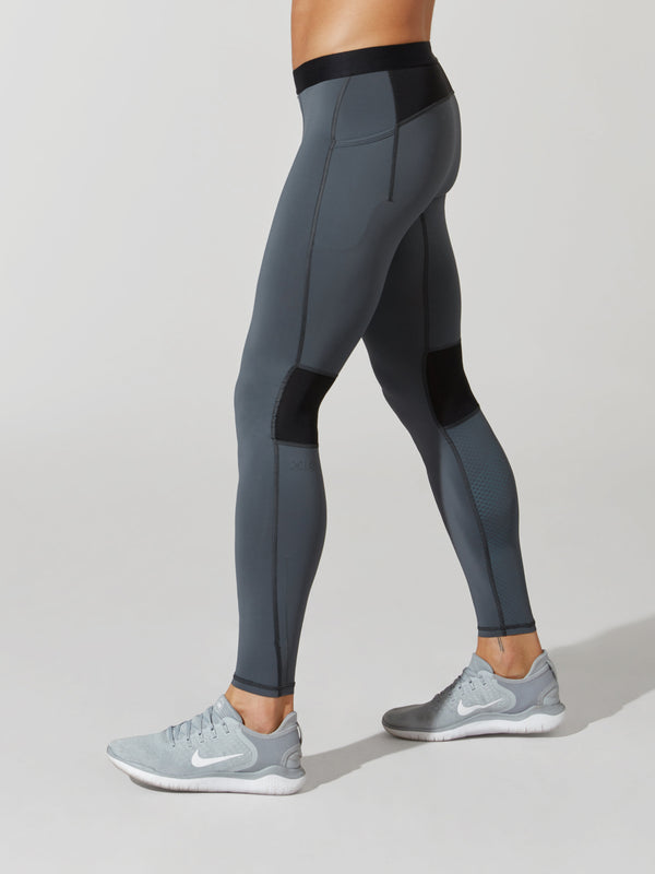 side view of male model in light grey full length leggings with black waistband and pocket detailing and light blue sneakers