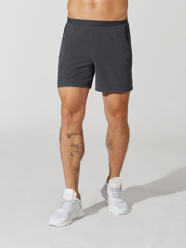 front view of male model in dark grey athletic shorts and white sneakers