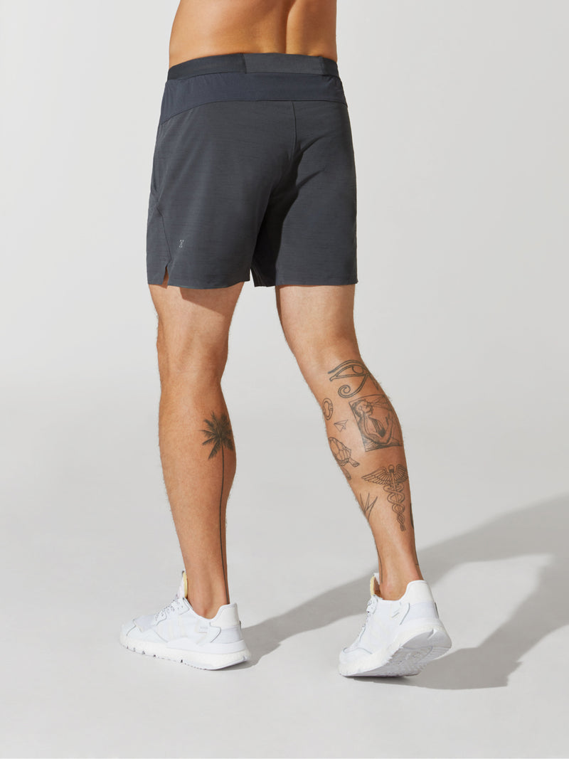 back view of male model in dark grey athletic shorts and white sneakers