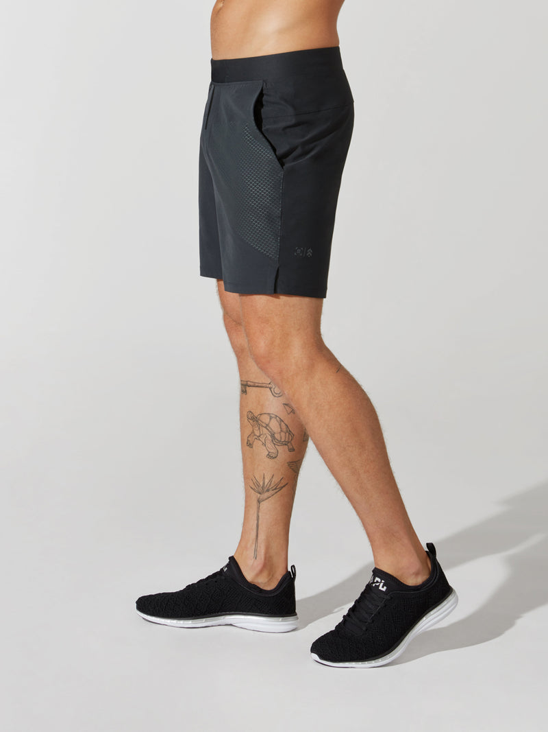 side view of male model in black athletic shorts and black sneakers