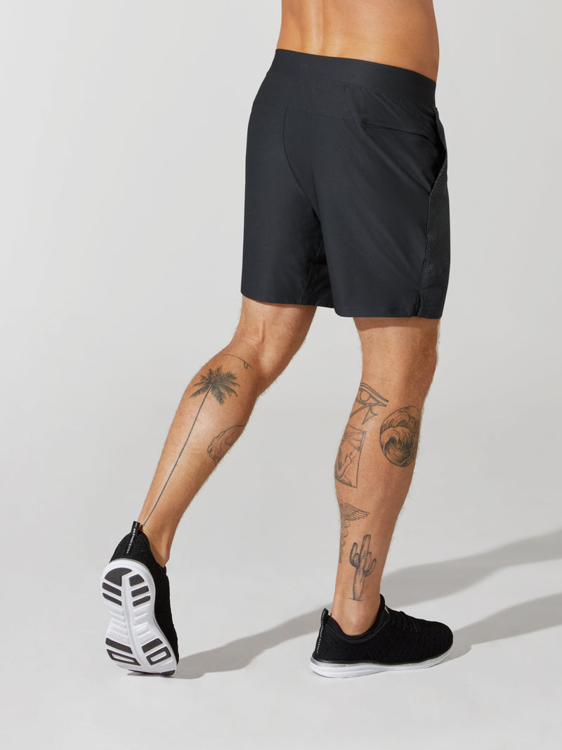 back view of male model in black athletic shorts and black sneakers