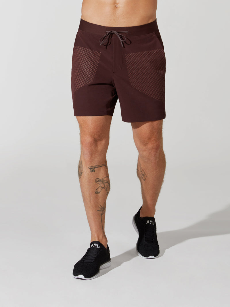 front view of male model in maroon athletic shorts and black sneakers