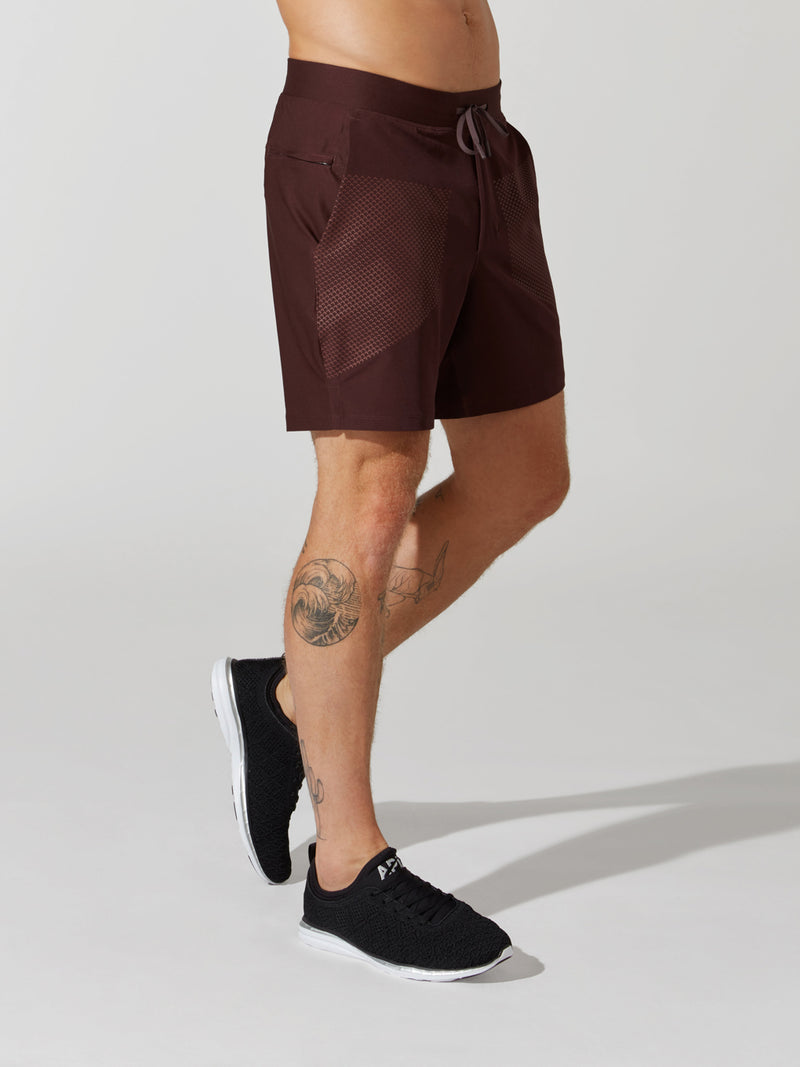 side view of male model in maroon athletic shorts and black sneakers