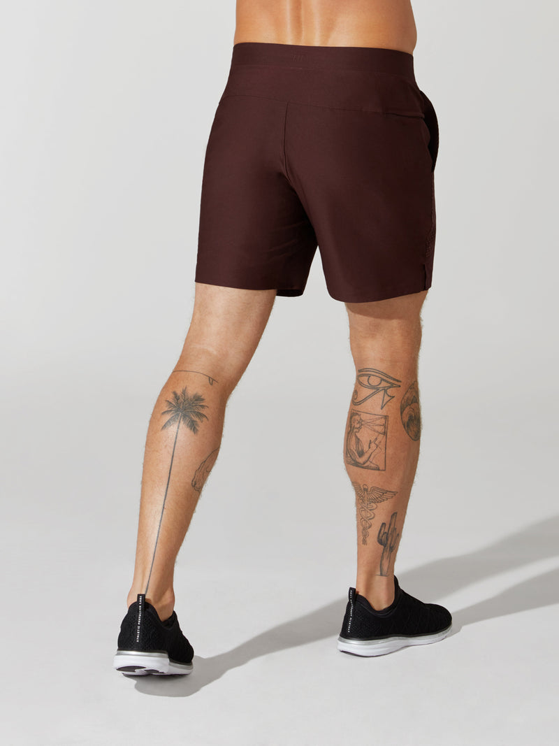 back view of male model in maroon athletic shorts and black sneakers
