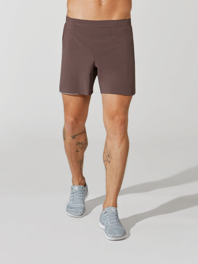 front view of male model in mauve athletic shorts and light blue sneakers
