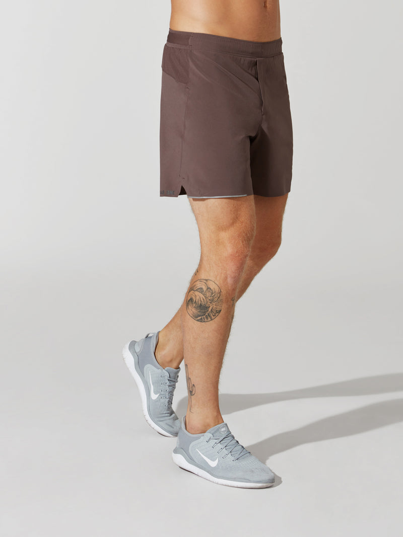 side view of male model in mauve athletic shorts and light blue sneakers