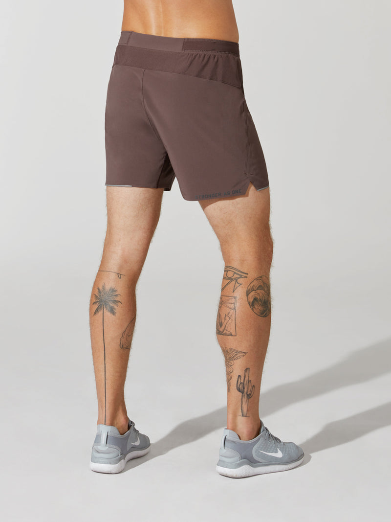 back view of male model in mauve athletic shorts and light blue sneakers