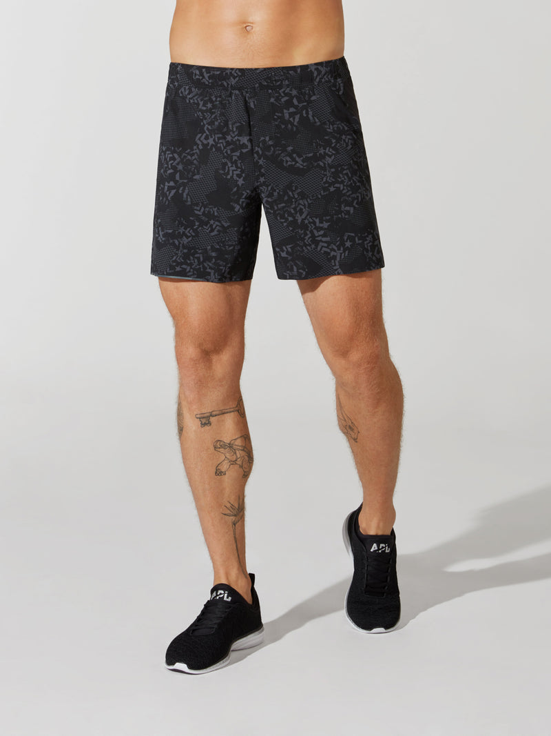 front view of male model in dark and light grey patterned athletic shorts and black sneakers
