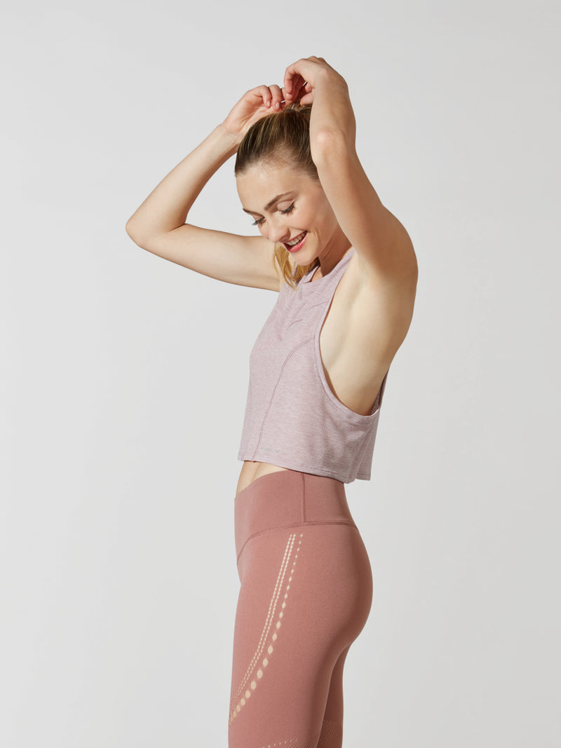side view of female model in light pink cropped tank top and mauve leggings with mesh detailing