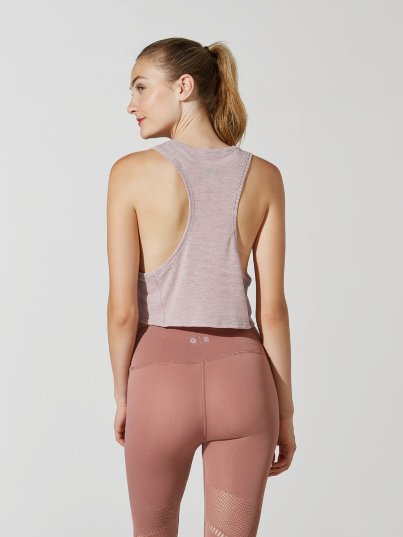 back view of female model in light pink cropped tank top and mauve leggings with mesh detailing