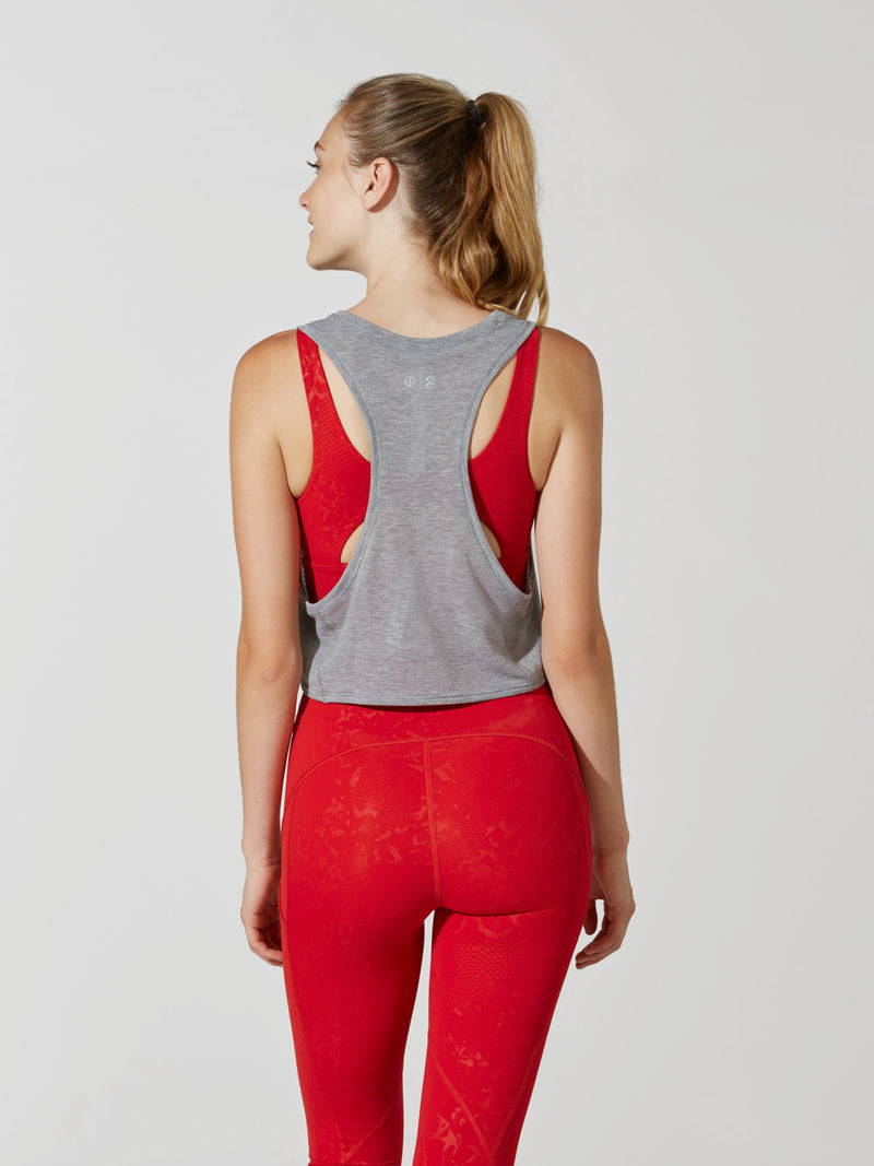 back view of female model in light grey cropped tank top and bright red leggings with embossed detailing