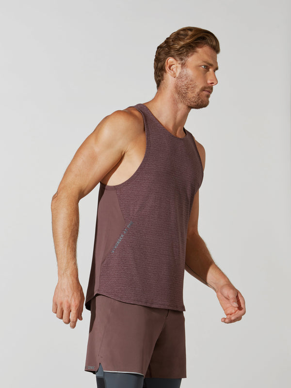 side view of male model in heather maroon tank top and matching athletic shorts