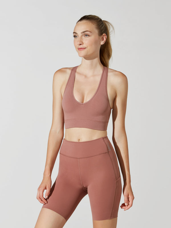 front view of female model in mauve low-cut sports bra and matching athletic biker shorts
