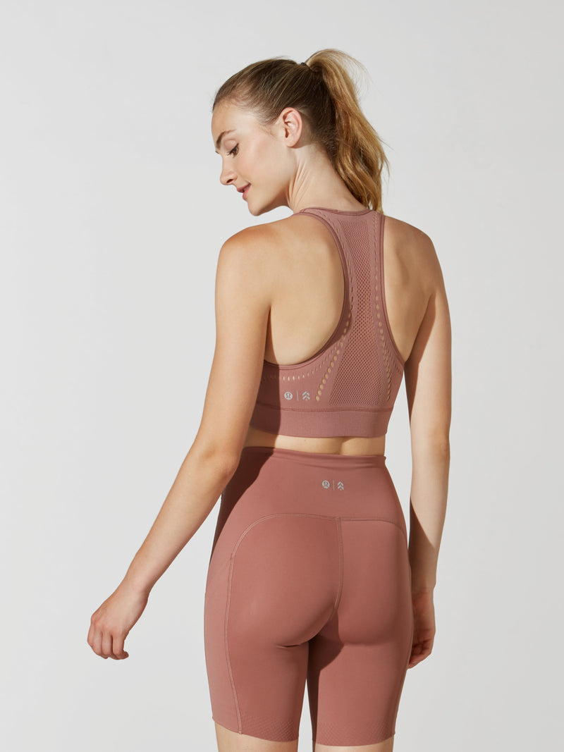 back view of female model in mauve racerback sports bra and matching athletic biker shorts