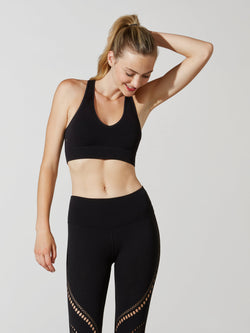 front view of female model in black sports bra and matching leggings with cutout detailing on thigh