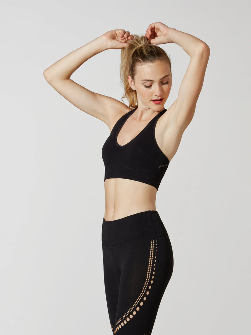 side view of female model in black sports bra and matching leggings with cutout detailing on thigh