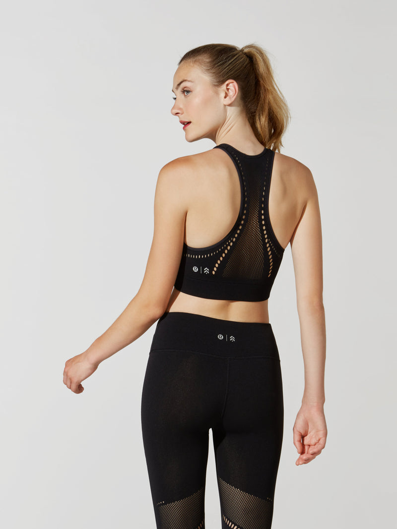 front view of female model in black sports bra with cutout detailing on back and matching leggings with cutout detailing on thigh