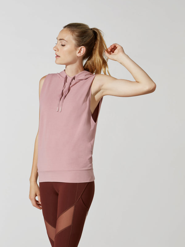 side view of female model in sleeveless mauve hoodie and maroon leggings