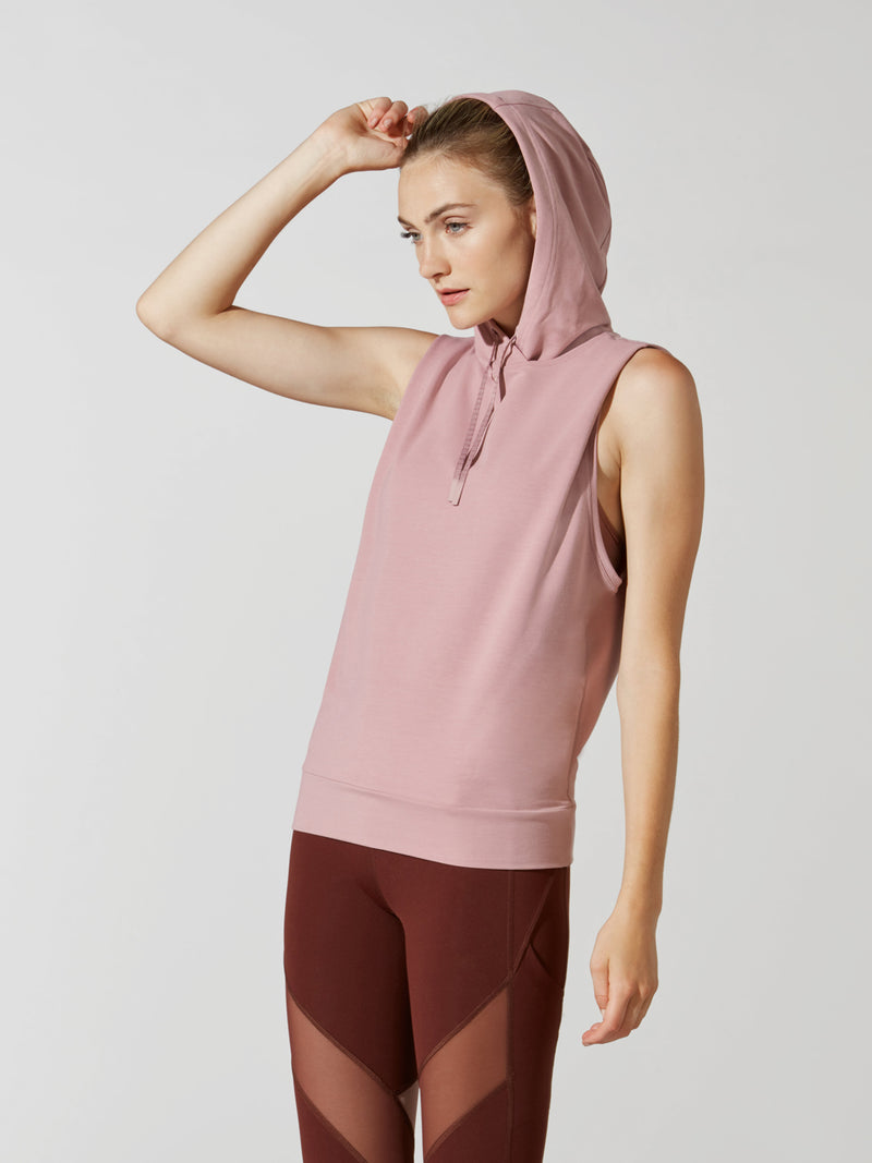 front view of female model in sleeveless mauve hoodie with hood up and maroon leggings