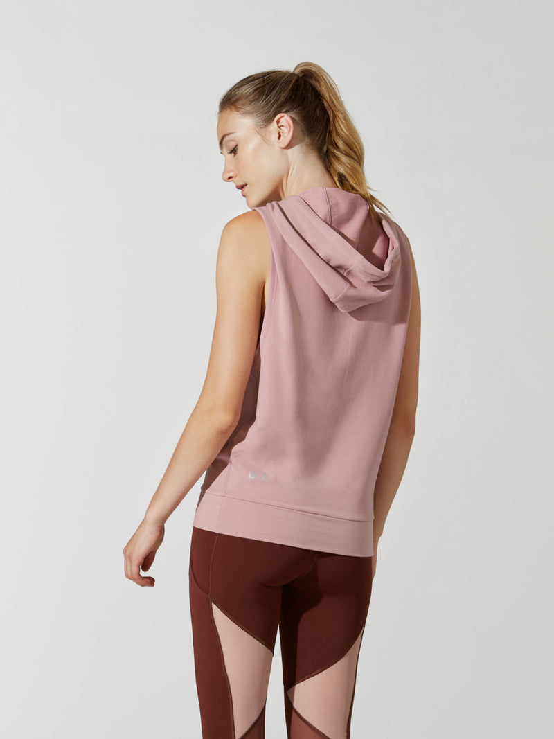 back view of female model in sleeveless mauve hoodie and maroon leggings