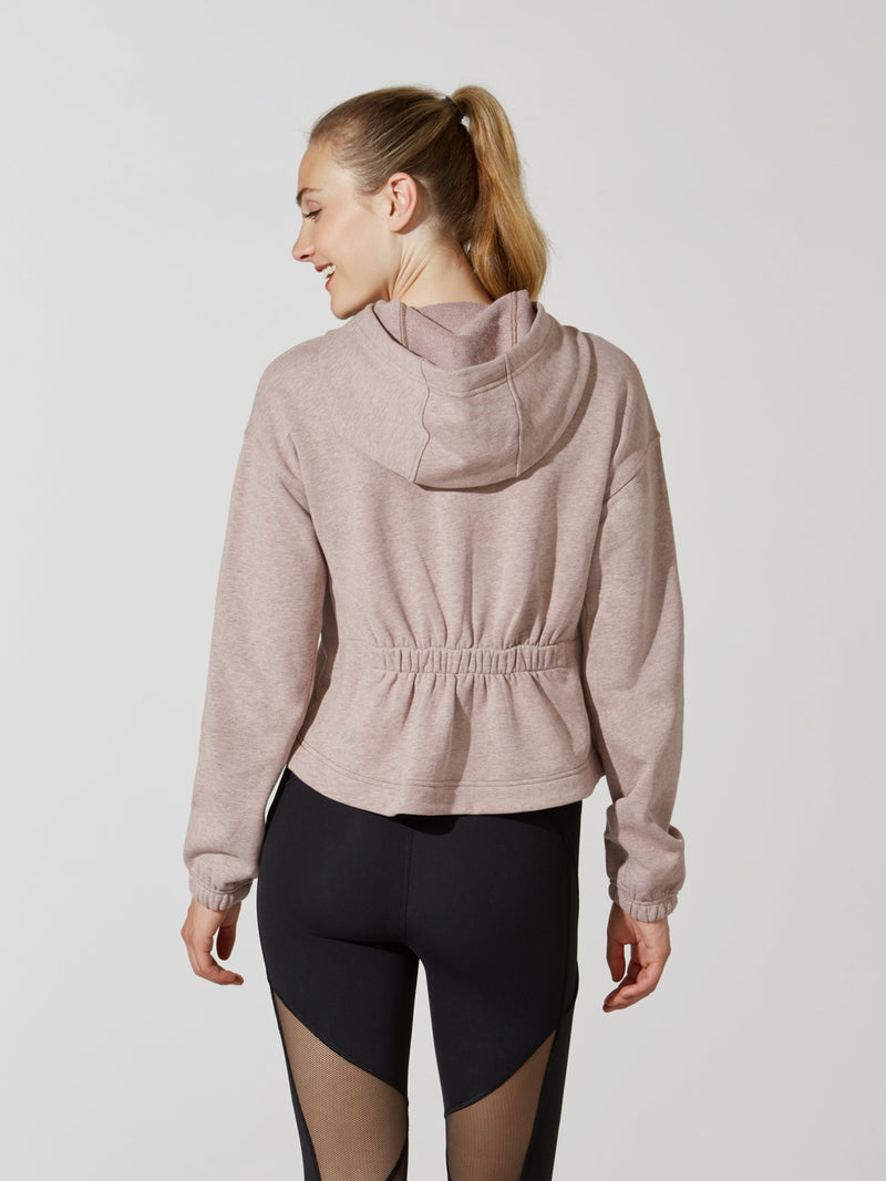 back view of female model in sand cropped long sleeve hoodie with cinched back and black leggings with mesh detail on thigh
