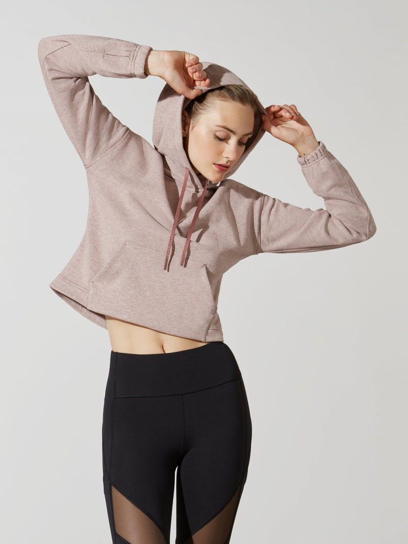 front view of female model in sand cropped long sleeve hoodie with arms up and black leggings with mesh detail on thigh
