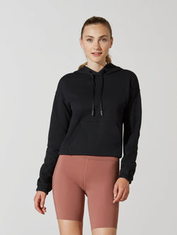 front view of model in black cropped long sleeve hoodie and mauve athletic biker shorts